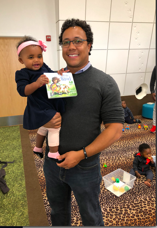 Father and daughter at the library during story time.