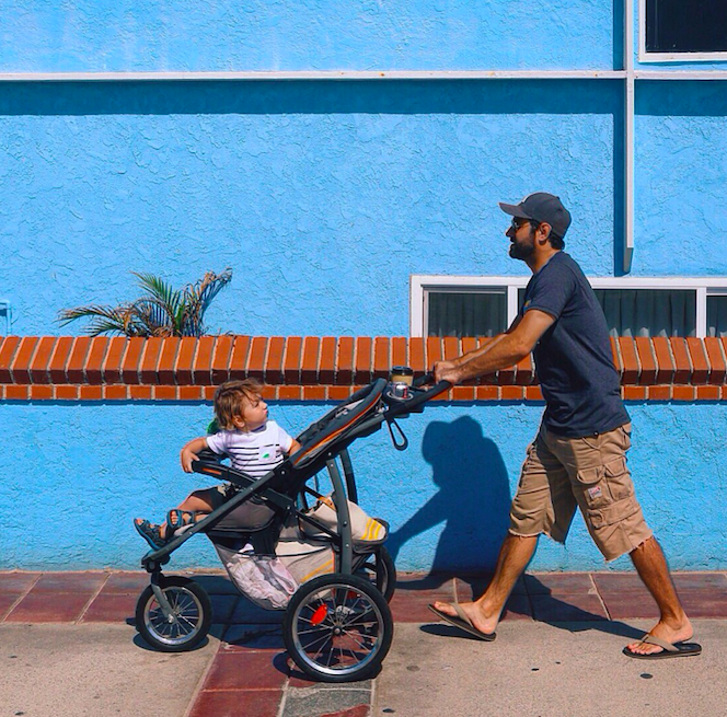 A dad pushing a stroller wearing cargo shorts.
